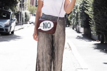 Pleated shiny trousers and text crossbody bag